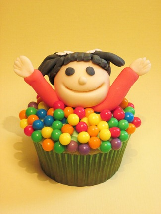 A cupcake decorated with a little girl playing in a ball pit