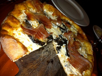 Pizza topped with mozzarella, speck, portobello mushrooms and truffle oil